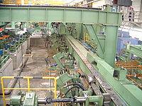 Sicht auf die Einlaufseite einer PQF®-Anlage: Einstößer (vorne rechts im Bild) und Rückhaltevorrichtung (hinten mittig im Bild)